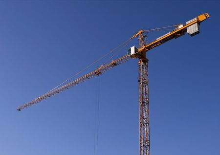 dragline: Industrial construction development. Yellow steel crane against blue sky.