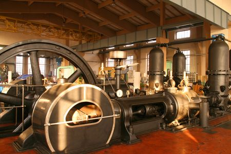 pumping: Vintage steam powered water pumping machine. Industrial machinery - building interior.