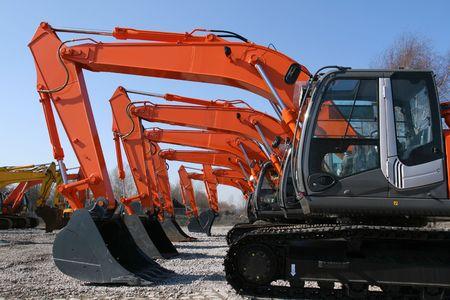New, shiny and modern orange excavator machines. Construction industry machinery.