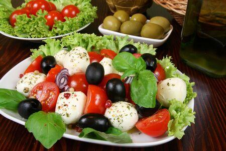Caprese - Italian salad with cherry tomatos, olives and mozarella cheese Stock Photo