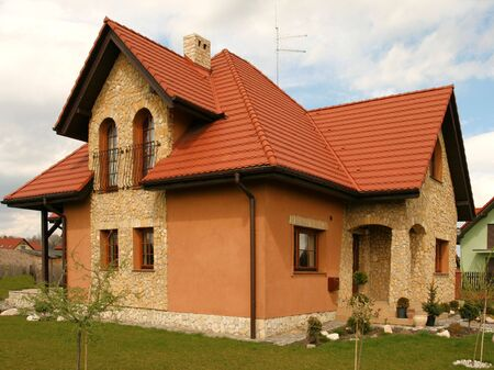 sloping: Beautiful home in Poland, Europe. Green lawn, red roof. Stock Photo
