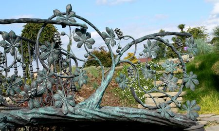 Metal fence decoration - wrought iron gate. Garden in background. photo