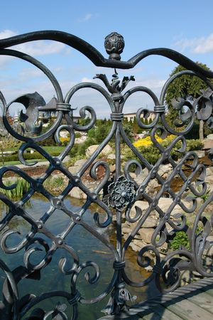 Metal fence decoration - wrought iron gate. Garden in background. Stock Photo