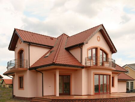 sloping: Orange home with red tiled roof. Nice architecture.