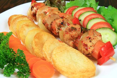 Shish kebab - delicious meat cuisine with chicken, onions and peppers. Cucumbers, tomatos and potato rings. photo