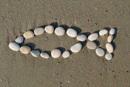 christian fish: S�mbolo cristiano de piedras sobre la arena - la forma de pescado  Foto de archivo