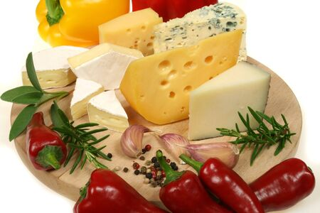 food photography: Cheese, peppers and herbs on a wooden board. Food photography.