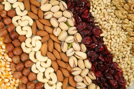 dries: Nuts and corn - hazelnuts, cashews, almonds, pistachios, dried cranberry and walnuts background. Dry food. Stock Photo