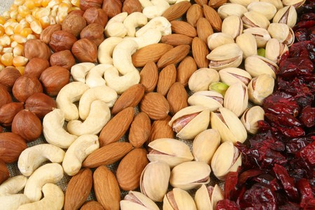 cashews: Nuts and corn - hazelnuts, cashews, almonds, pistachios, dried cranberry and walnuts background. Dry food. Stock Photo