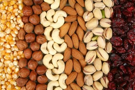 Noten en maïs - hazelnoten, cashewnoten, amandelen, pistachenoten achtergrond, gedroogde cranberries. Droogvoer.