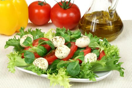arugula: Healthy and colorful vegetable salad. Tomato, rocket plant (arugula) and mozzarella with herbs.
