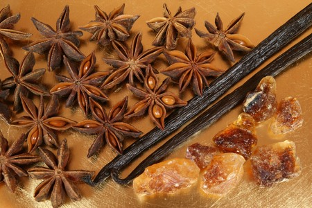 aniseed: Star aniseed or badiane and vanilla on the golden plate. Stock Photo