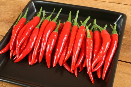 capsaicin: Red hot chilli peppers on the black plate.