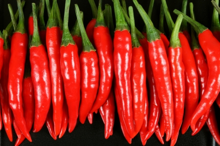 Red hot chilli peppers on the black background.