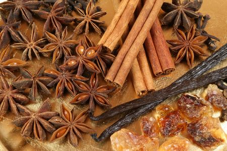 aniseed: Star aniseed , vanilla beans and cinnamon on a gold plate.