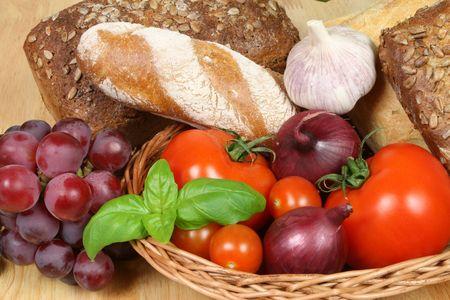 european food: Europea en una canasta de alimentos - tomates, cebolla, albahaca, el pan y las uvas.