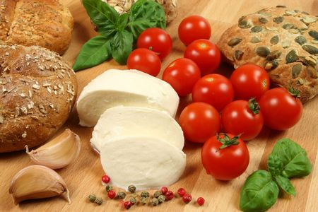 Mozzarella cheese, tomatoes, garlic, fresh basil and pepper. Bread and ingredients for a salad. Stock Photo