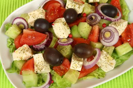 greek cuisine: Greek salad. Vegetarian appetizer. Colorful food. Feta cheese, cucumbers, onions, tomatoes and black olives. Stock Photo