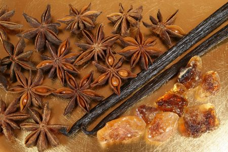 badian: Star aniseed or badiane and vanilla beans on the golden plate.