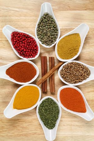 Whole variety of colorful spices. Assortment of cuisine ingredients in ceramic containers. photo