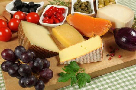 Varieties of hard cheese on a wooden board. Grapes and nuts. Stock Photo