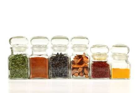 food additives: Glass jars with colorful herbs and spices. Turmeric, pepper, ramsoms, juniper. Stock Photo
