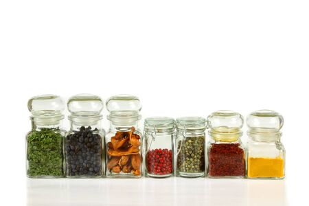 juniper: lass jars with colorful herbs and spices. Turmeric, pepper, ramsoms, juniper. Stock Photo