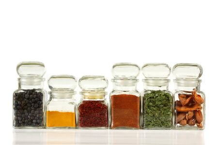 Glass jars with colorful herbs and spices. Turmeric, pepper, ramsoms, juniper. Stock Photo - 7094902
