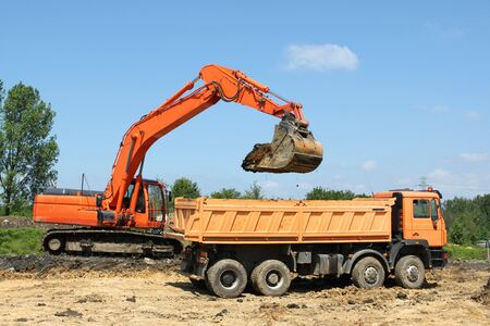 earth road: Road construction works in Poland. Heavy machinery - excavator and dump truck.