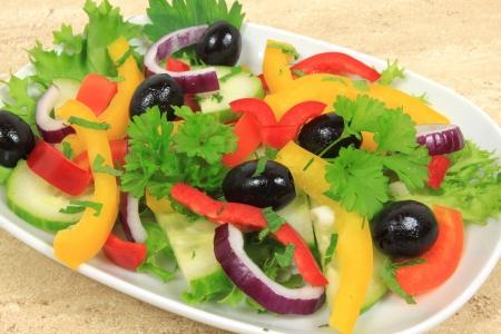 Salade met paprika, zwarte olijven en rode ui.