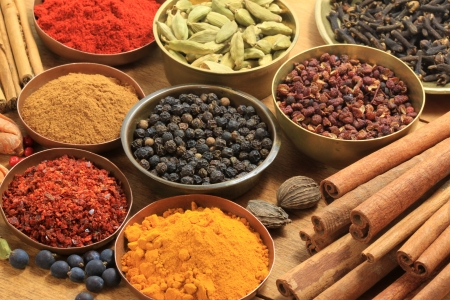Cooking ingredients - warm colours of herbs and spices. Cinnamon sticks, cardamon, allspice, clove, mace, fenugreek, coriander and juniper