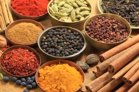 Koken ingrediënten - warme kleuren van kruiden en specerijen. Kaneelstokjes, kardemom, piment, kruid nagel, foelie, fenegriek, koriander en jenever bes  Stockfoto