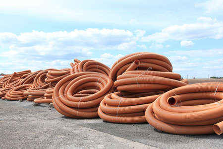 Orange plastic tubes - construction site objects. PVC sewer pipes. photo