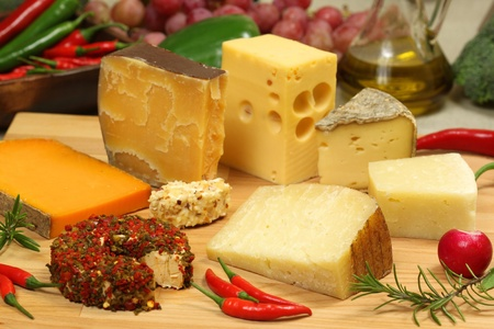 Delicacies. Food composition - hard and soft cheese varieties and vegetables. photo