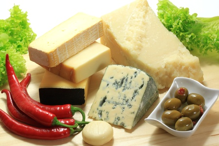 Various types of cheese on a wooden board.