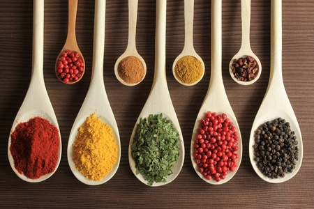 Colorful spices in wooden spoons - beautiful kitchen image. Stock Photo - 9418849