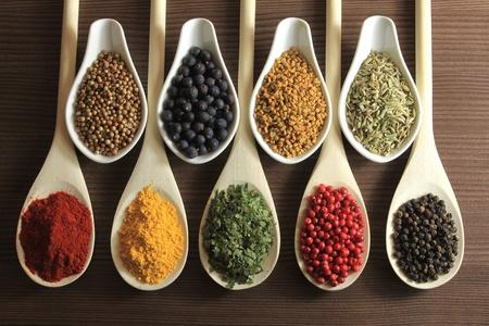 especias: Hierbas y especias en cucharas de madera - imagen de hermosa cocina. Foto de archivo