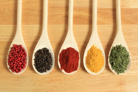 Colorful spices in wooden spoons - beautiful kitchen image. Stock Photo - 9598484