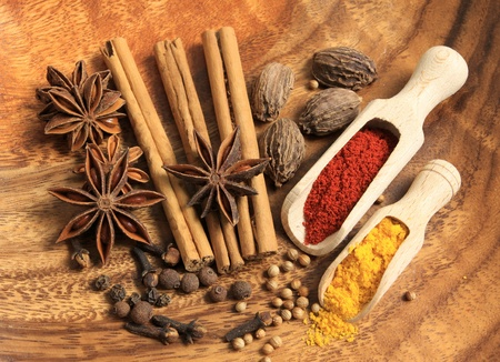 Cooking ingredients: cinnamon sticks, clove and star anise. Red powdered pepper and yellow turmeric. photo