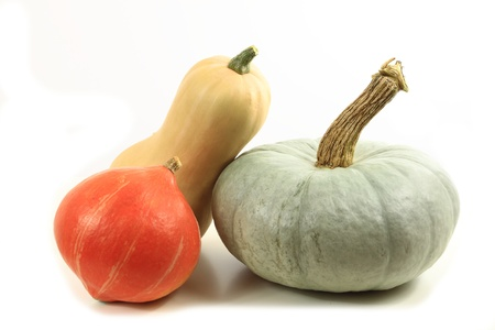 gourds: Different types of pumpkins on a white table. Stock Photo