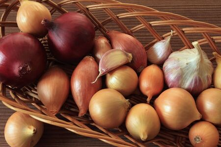 Basket of onions and garlic. Vegetables for cooking. photo