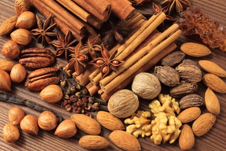 Christmas spices. Cooking ingredients: cinnamon sticks, clove and star anise. Various nuts. Stock Photo