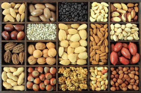 cashew: Varieties of nuts and other seeds: peanuts, hazelnuts, chestnuts, walnuts, cashews, pistachio, almonds, coffee, sunflower seeds and pecans. Food and cuisine. Stock Photo