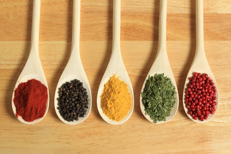 Colorful spices in wooden spoons - beautiful kitchen image. photo
