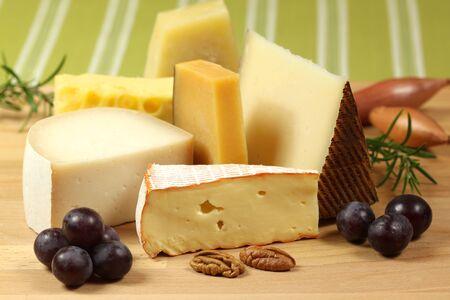 queso de cabra: Variedades de queso duro en una tabla de madera. Foto de archivo