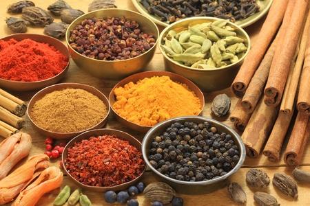 Ingredients - warm colours of herbs and spices. Cinnamon sticks, cardamon, allspice, clove, mace, fenugreek, coriander and juniper photo