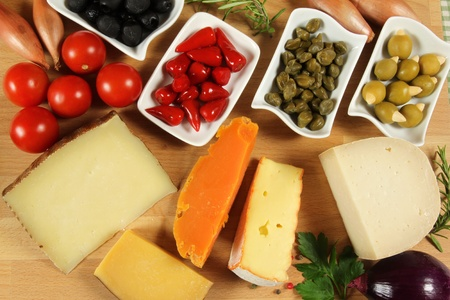 Varieties of hard cheese on a wooden board. Various food ingredients. photo