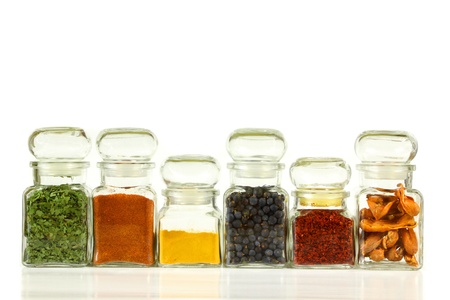 juniper: Glass jars with colorful herbs and spices. Turmeric, pepper, ramsoms, juniper. Stock Photo
