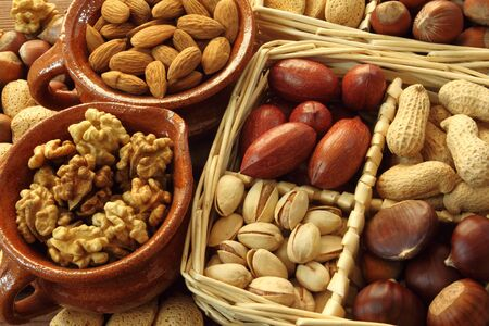 Varieties of nuts: peanuts, hazelnuts, chestnuts, walnuts,  pistachio and pecans. Food and cuisine. Stock Photo - 13300632