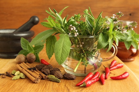 Spices and bunch of fresh aromatic herbs in glass. photo